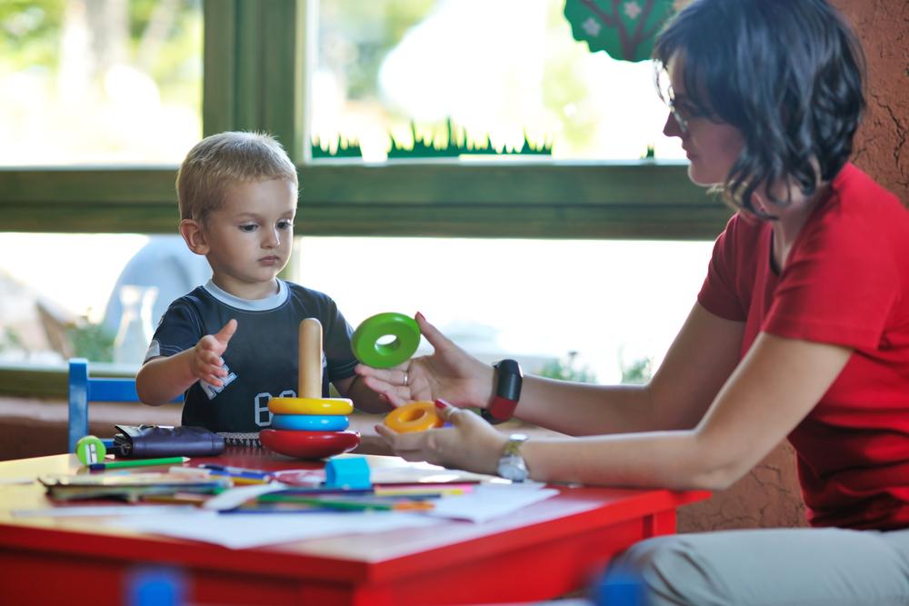 Przedszkolanka bawi się zmałym dzieckiem, razem układają kolorowe klocki.