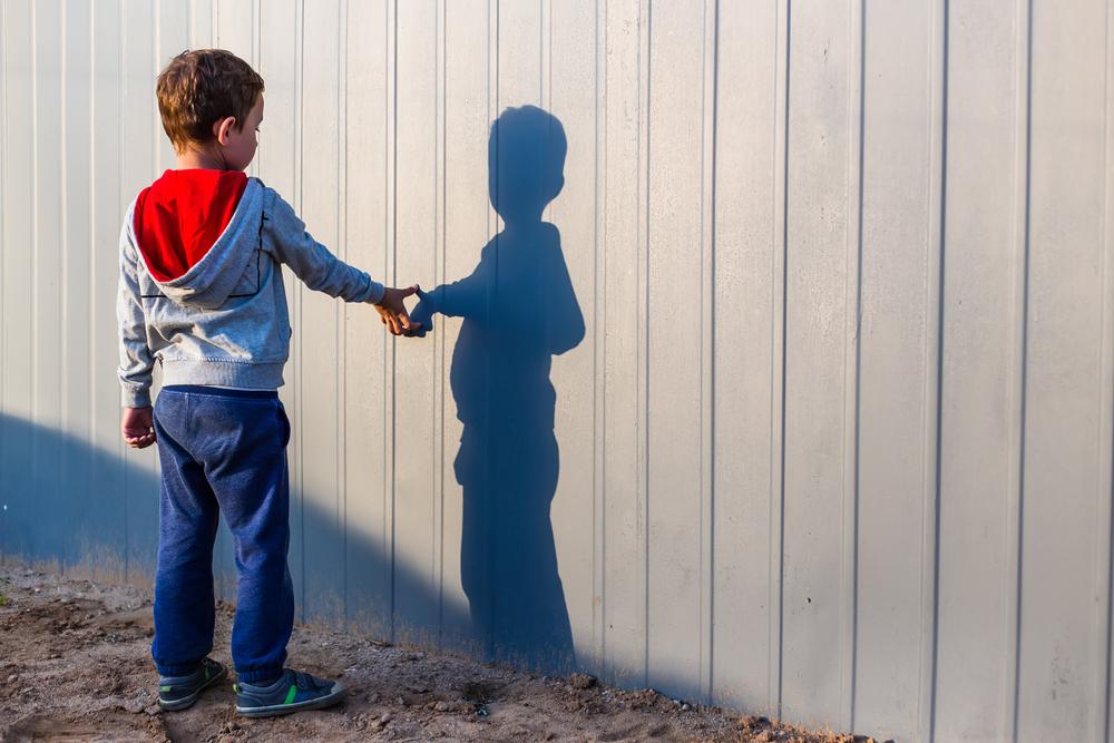 z prawej strony stoi chłopiec, chory na<strong>autyzm</strong>, jest sam