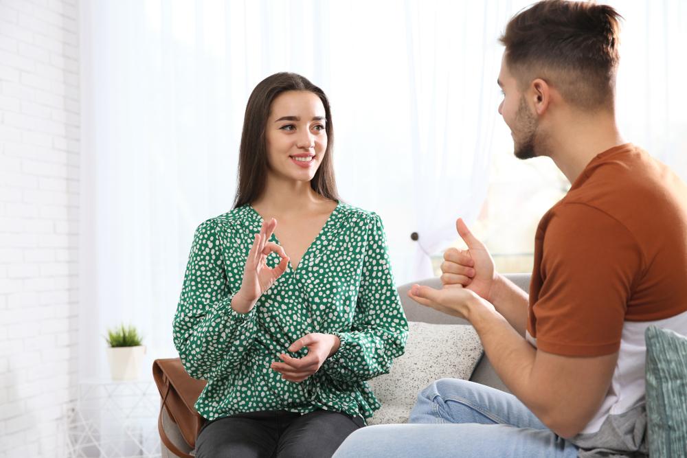 Młoda kobieta imłody mężczyzna siedzą naprzeciwko siebie, pokazują sobie znaki języka migowego