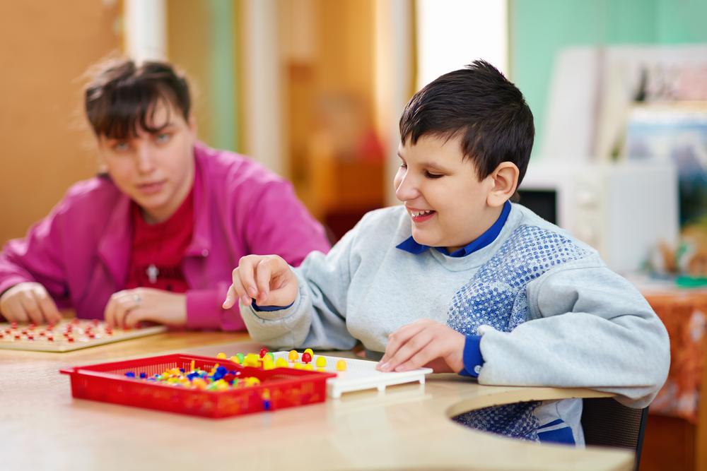 z prawej strony dziewczynka ichłopiec grają wgre edukacyjną, każde znich cierpi nachorobę genetyczną
