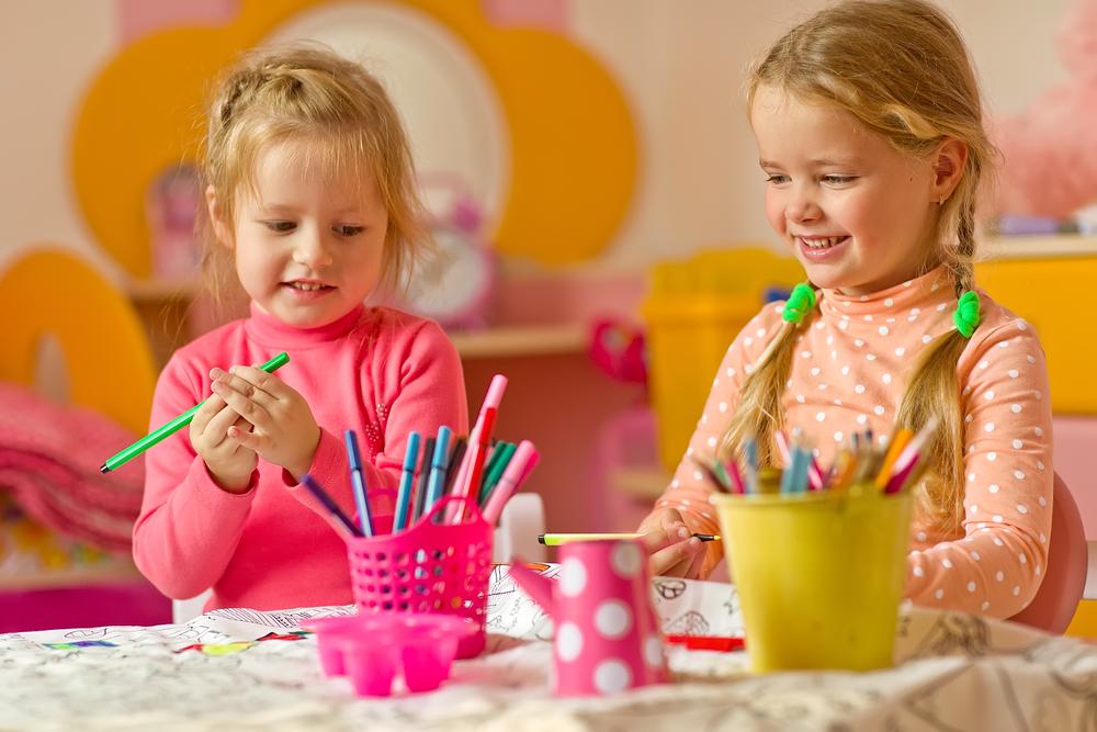 z prawej strony znajdują się dwie dziewczynki, uśmiechnięte siedzą przy stoliku, trzymają kredki irysują
