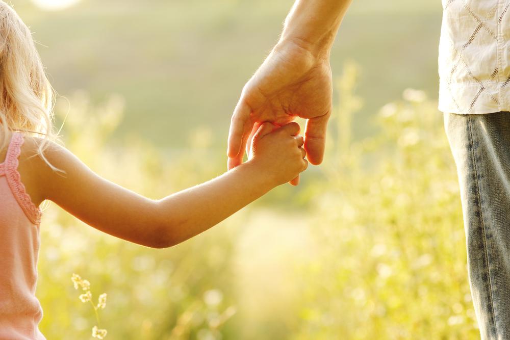 Rodzic trzymający córkę zarękę