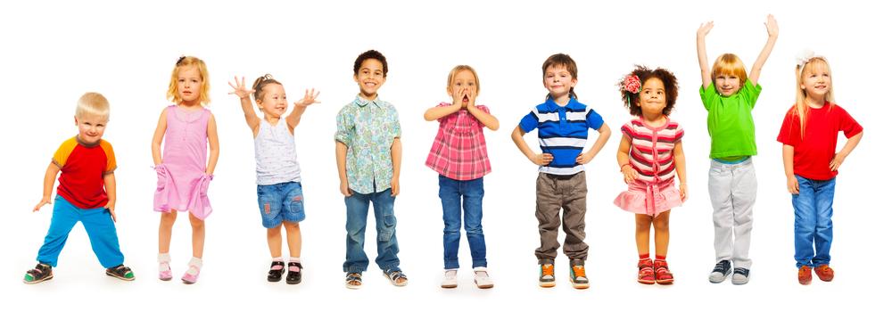 Grupa małych dziewczynek ichłopców stoi obok siebie nabiałym tle, wszyscy są uśmiechnięci izadowoleni.