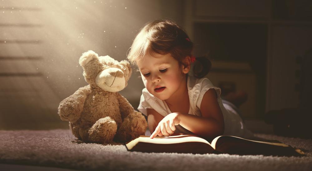 Dziewczyna zpluszowym misiem czyta książkę