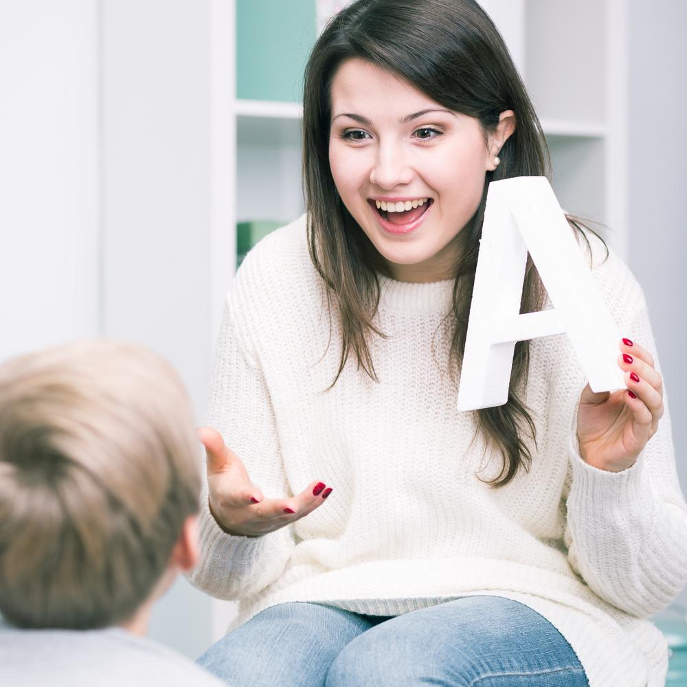 Logopeda naterapii zdzieckiem, uczy dziecko wymawiać samogłoskę A