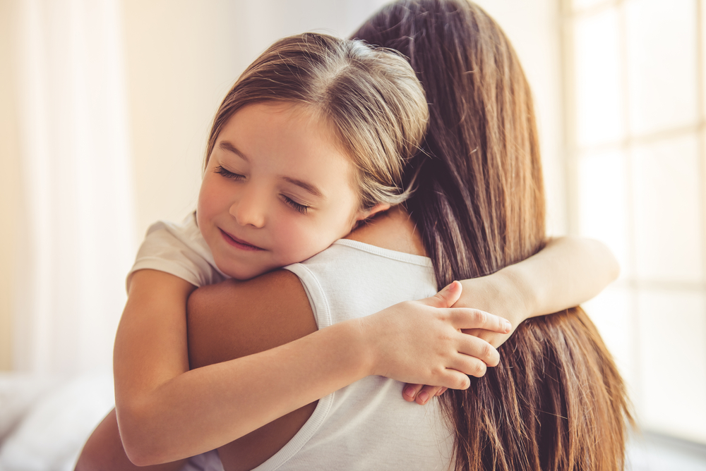 Logopeda przytula uśmiechnięte dziecko podczas terapii