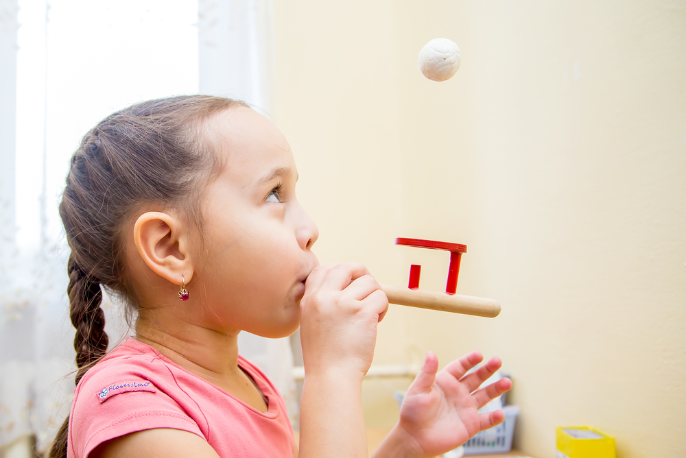 Dziewczynka wykonuje ćwiczenia oddechowa w<strong>gabinecie logopedycznym</strong>