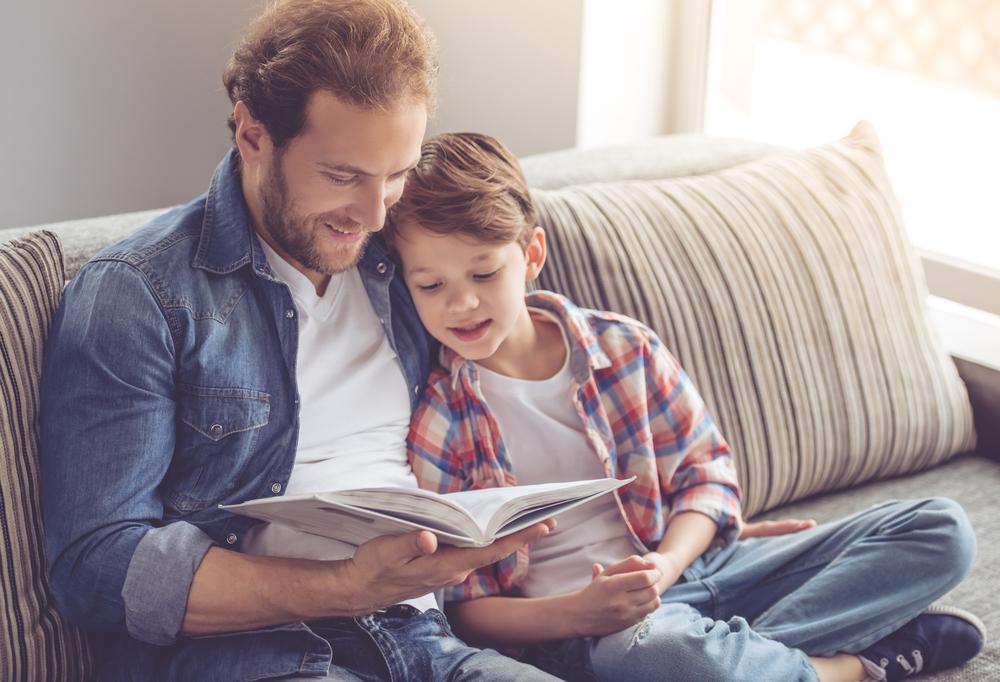 z lewej strony znajduje się ojciec zmałym synem, razem czytają książkę