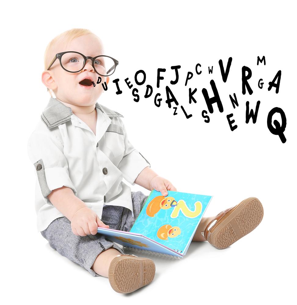 Mały chłopiec wokularach wypowiada głoski, trzyma wręku książeczkę