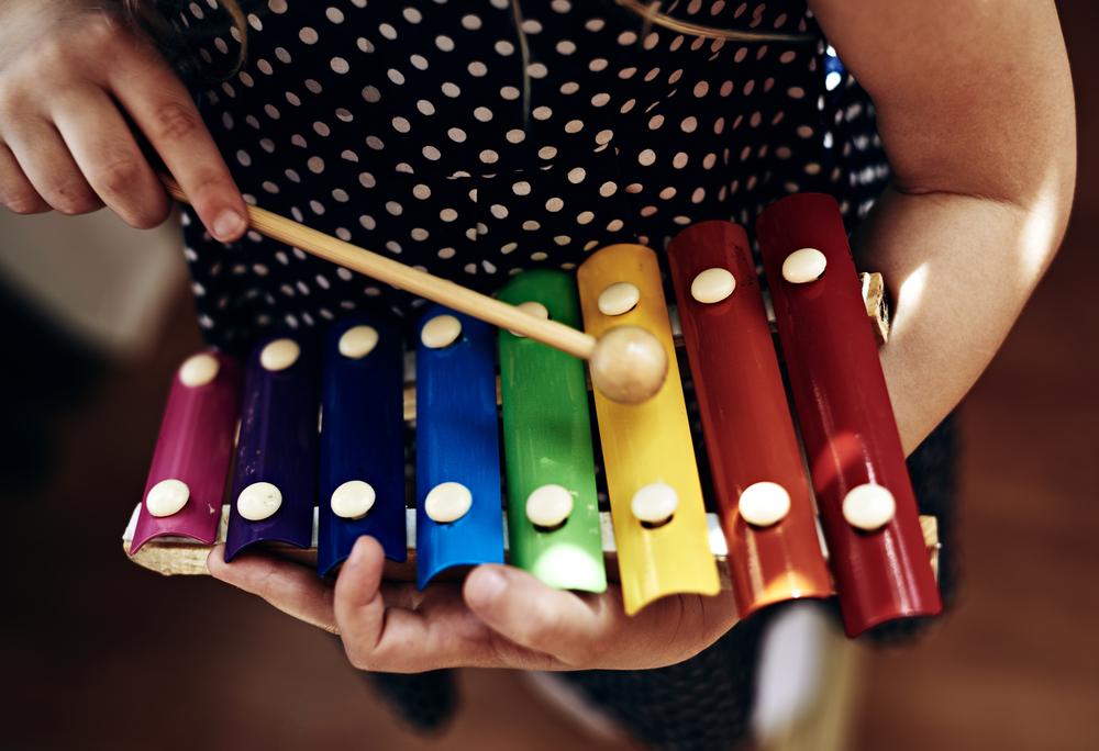 dziewczynka trzyma kolorowe dzwonki igra nainstrumencie