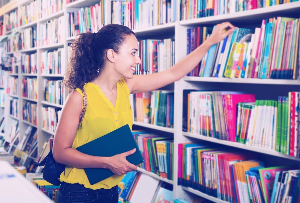 Studentka logopedii znajduje się wbibliotece, szuka książek, które pomogą jej wnauce