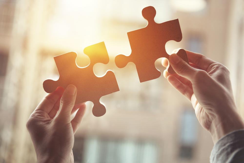 Dłonie trzymające puzzle, symbol złożonego problemu <strong>autyzm</strong>u