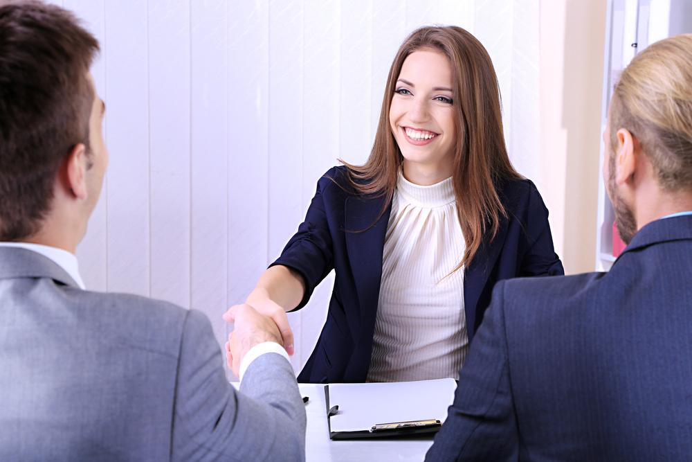 Szczęśliwa studentka narozmowie kwalifikacyjnej, wita się zegzaminatorami