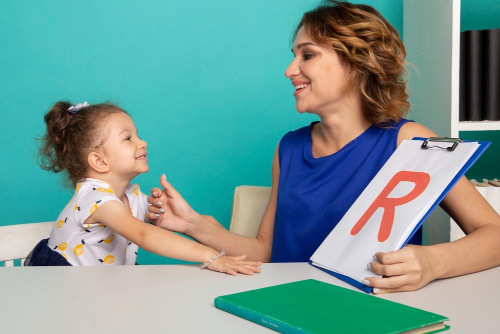 """Logopeda uczy dziecko mówić głoskę """"r"""""""