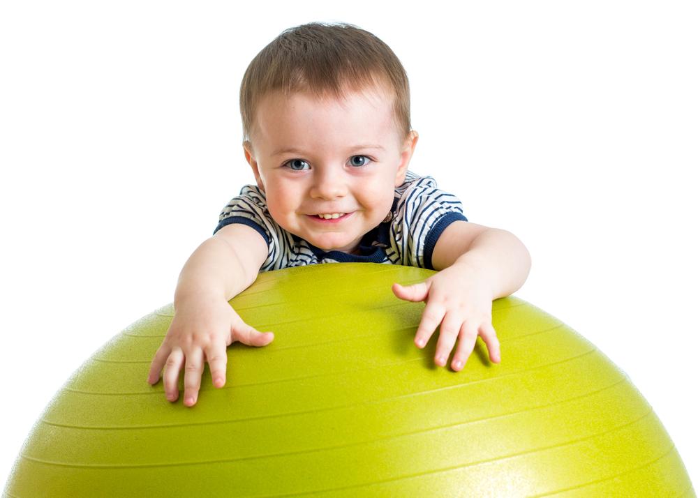 Chłopiec wykonuje ćwiczenia na piłce