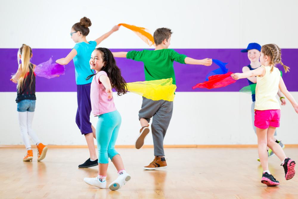 Grupa dzieci z logopedą wykonują ćwiczenia logorytmiczne