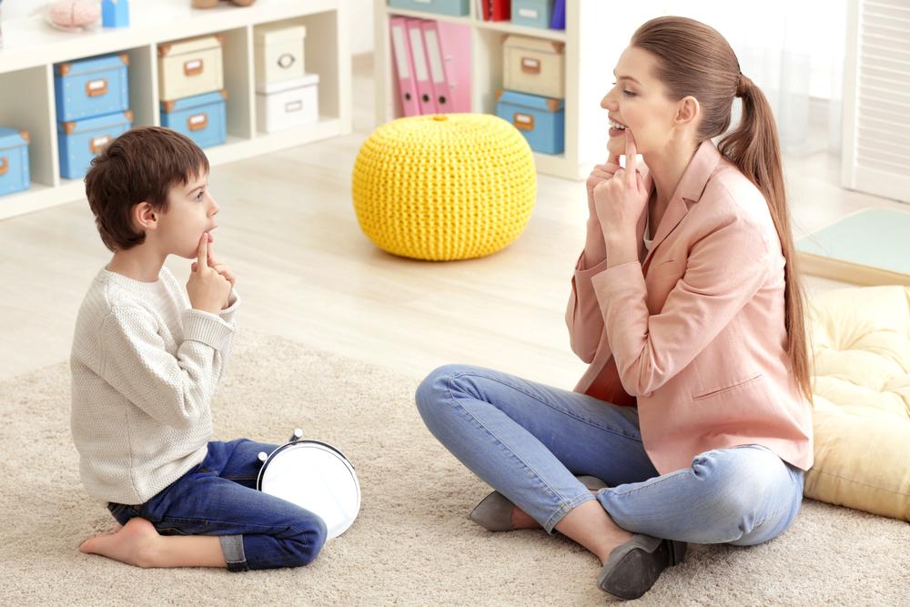 Młody logopeda prowadzi ćwiczenia z dzieckiem