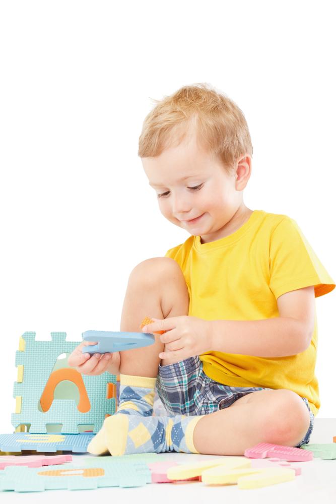 Mały chłopiec bawi się układanką